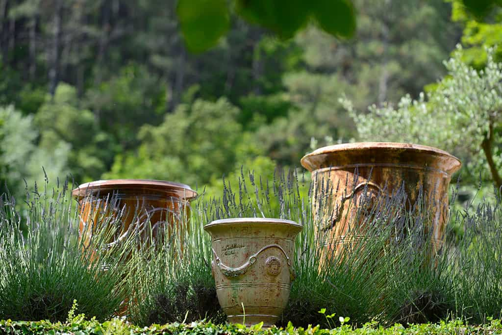 3 Anduze vases staged in a garden
